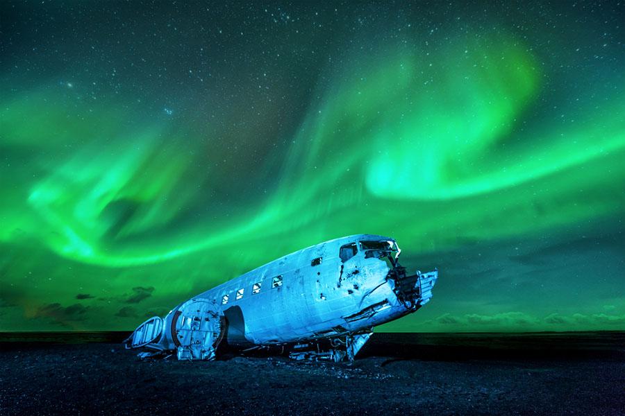 İzlanda'ya İlk Yerleşim Ne Zaman Gerçekleşti? 1973 yılında yakıtı biterek düşen bir uçağın arka silüette Kuzey Işıkları manzarasıyla görünümü..