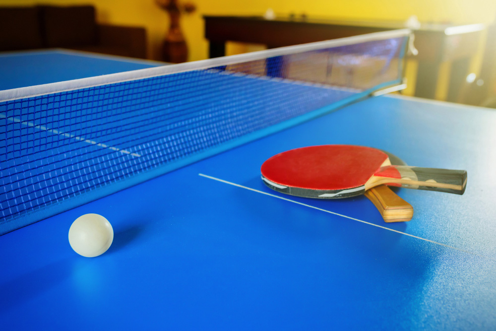 Masa Tenisini Kim Buldu ? Mavi bir masa üzerinde top ve raketler..